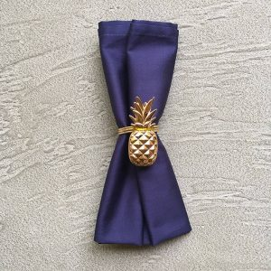 Gold pineapple napkin ring with navy napkin