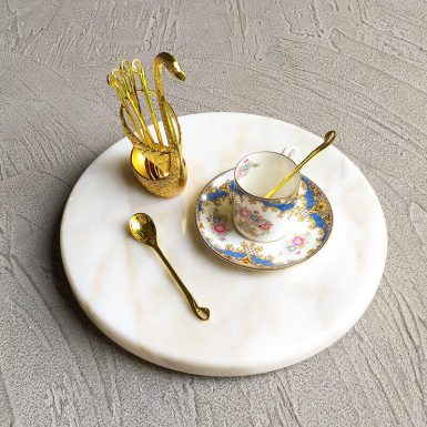 Gold swan with spoons and teacup and saucer