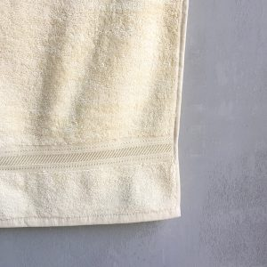 Hanging Creme colored towel with grey background.
