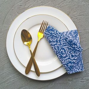 Folded Blue Napkins, White plates and Golden cutlery