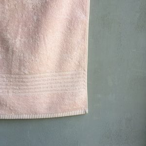 Hanging Powder pink towel with grey background.
