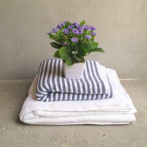 Folded Snow White Towel with grey and white stripes towel and artifical plant.