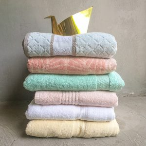 Bunch of folded towels: Pineapple patterned towel, Blush pink towel, Aqua Towel, Powder pink towel, Snow White Towel, Creme Colored Towel and Brass Origami Swan.
