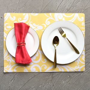 Yellow scrolls Placemats with white plates, gold cutlery, coral napkin and sparse gold geometric napkin ring.